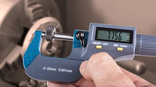 Someone holding a digital micrometre with a lathe in the background.