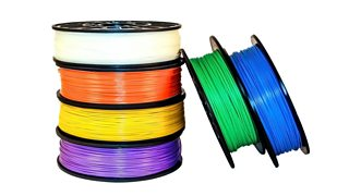 A stack of six coloured filament coils for 3D printing on a white backdrop.