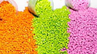 Three tubs of plastic pellets in orange, green and pink spilled out onto a white backdrop.