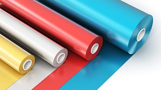 Four rolled out rolls of polyvinyl chloride (PVC) film in gold, silver, red and blue.