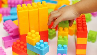A child's hand is shown building with an array of colourful plastic toy blocks.