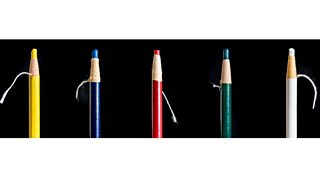 Five different coloured chinagraph wax pencils laid out against a black background.