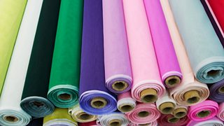 A birds-eye-view of a stack of fabric rolls in colourful shades.