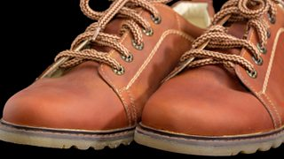A close-up image of the toes of a pair of brown men's shoes with eyelets.