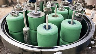 A chemical tank machine used for dying materials with rolls of fabric shown inside.