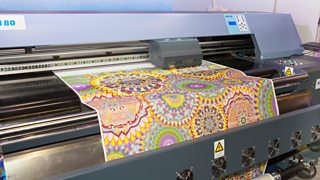 A machine showing digital printing of a detailed, colourful pattern on a fabric.