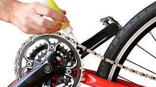 A man's hand shown oiling a bike chain.