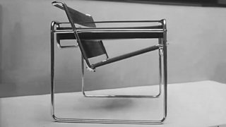 A black and white image of a metal framework chair.