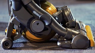 A close-up image of a modern Dyson vacuum cleanera with four wheels and a ball in the centre.