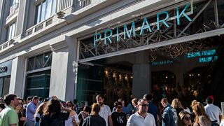 The front of a Primark store with a big crowd walking past outside.