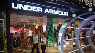 An Under Armour shopfront inside a shopping centre with two women walking past.