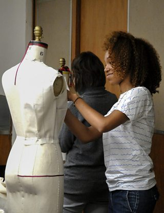 A college student draping a mannequin in a fashion design class.