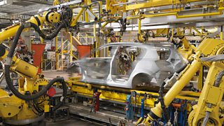 Multiple yellow robot arms working on building a silver car in a manufacturing plant.