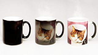 Three mugs displayed in a line - two have a cat's face on them showing colour change.