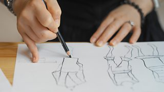 A pair of hands shown drawing a stretch of figures with a black pencil on white paper.