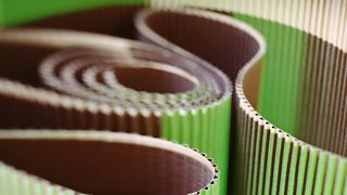 A close-up view of rolled up corrugated card in green and brown.
