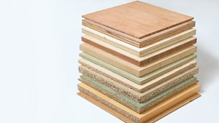 A stack of square boards of different manufactured wood in varying thicknesses.