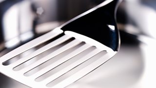 A close-up image of a stainless steel spatula used for cooking.