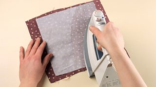 A pair of hands shown ironing a material onto a piece of burgundy polka dot fabric.
