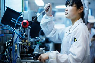 Worker at small parts manufacturing factory in China