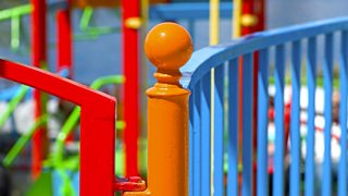 Metal apparatus around a playground have been painted in bright colours.