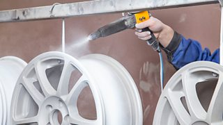 A metal car wheel rim is suspended from a bar while a hand powder coats it white.