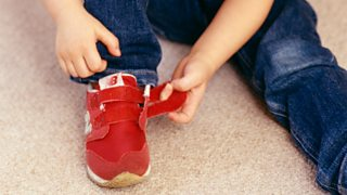 A young child sat on the floor fastening their red Velcro trainers.