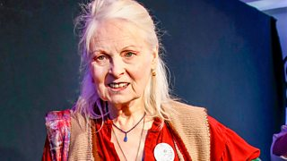 A photograph of Vivienne Westwood in front of a black backdrop with her arm on her hip.