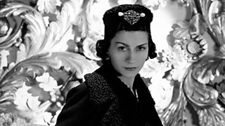 A black and white photograph of Coco Chanel wearing a coat and hat.