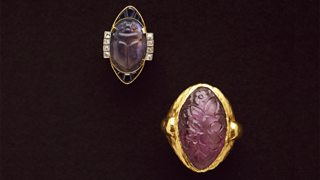 Two gold and precious stone Art Nouveau rings are displayed side by side.