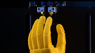 A yellow plastic model of a prosthetic hand being 3D printed.