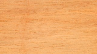 The texture of jelutong wood - reasonably pale orange with darker lines running through.