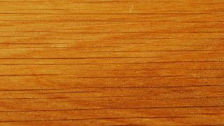 The texture of larch wood - vibrant orange brown with darker lines running through.