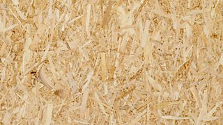 The texture of chipboard - wood chips of varying shades are glued together.