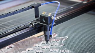 A laser cutter cuts small shapes into a piece of clear acrylic plastic.