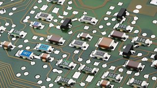 Many small and numbered electronic components have been soldered onto a circuit board.