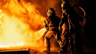 Two firefighters fight off a large blaze with water from a hose.