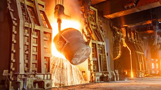 Molten steel being poured from a large metal cauldron, causing sparks, in a steel production plant.