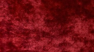 A close-up of a patchy pile weave within a red velvet fabric.