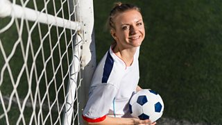 A female footballer is sat with a football next to a goal.
