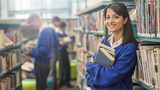 A girl holding books in a school library