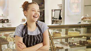 Girl wearing apron smiling behind bakery