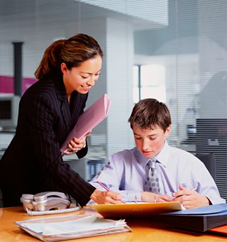 Businesswoman talking to boy with files on desk in office
