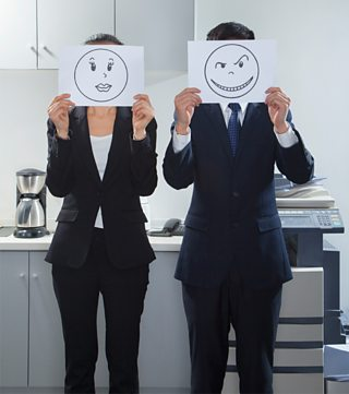 A businesswoman and businessman stood side by side holding smiley faces on paper.
