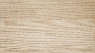 The texture of ash wood - pale with slightly darker lines running through.