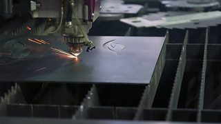 A close-up image of a laser cutter cutting shapes from a piece of metal.