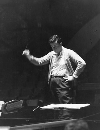 A photograph of Malcolm Arnold conducting.