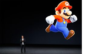 A member of the Nintendo company and a projected image of Super Mario.