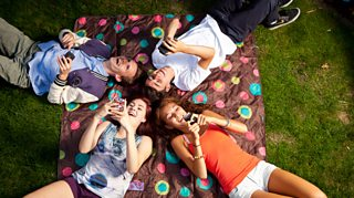 Teenagers using mobile phone and laughing