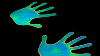 A pair of hands showing a blue/green thermochromic pigment against a black backdrop.